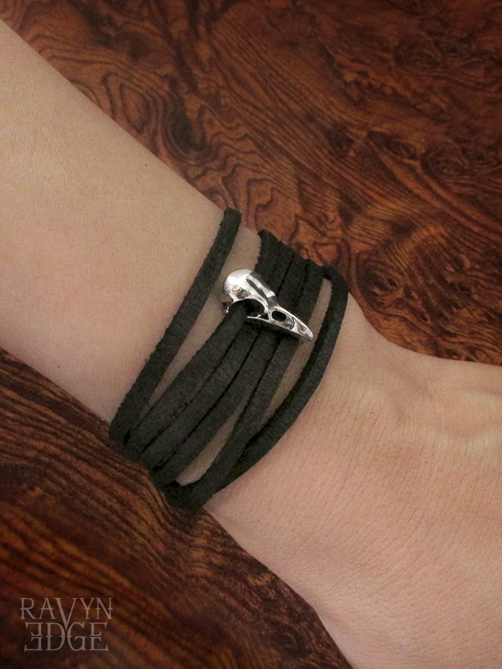 Tiny sterling silver raven skull charm on a black leather wrap bracelet