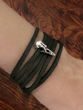 Leather wrap bracelet with tiny silver raven skull on a womans wrist